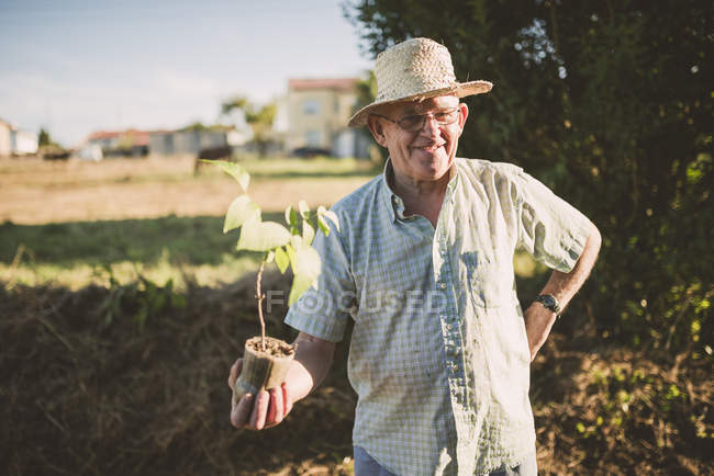 Portrait of smiling farmer with straw hat holding a plant in hands — Stock Photo