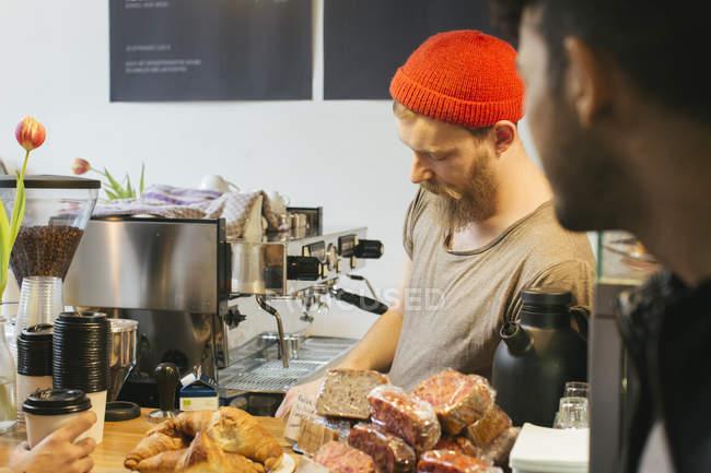 Barista behind cafe counter — Stock Photo