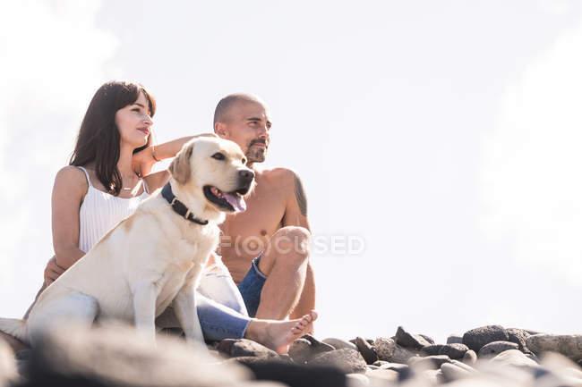 Coppia seduta con il cane sulla spiaggia rocciosa — Foto stock