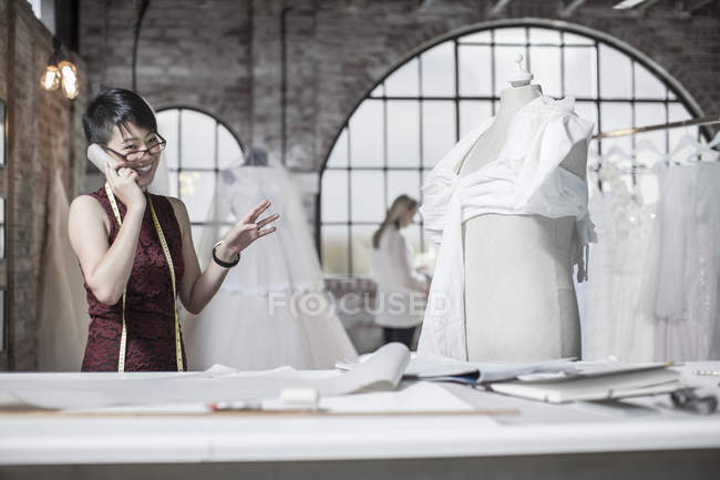 Wedding dress designer talking on phone in bridal store — Stock Photo