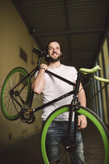 Sorrindo jovem carregando fixie bicicleta — Fotografia de Stock