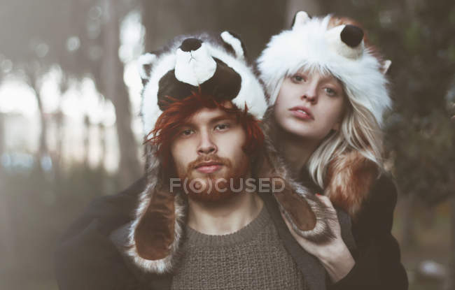 Portrait de jeune couple portant des chapeaux de l'animal dans les bois — Photo de stock
