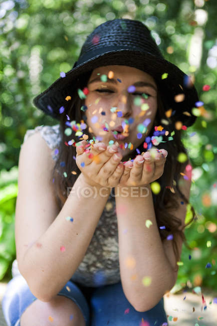Young woman playing with confetti — Stock Photo