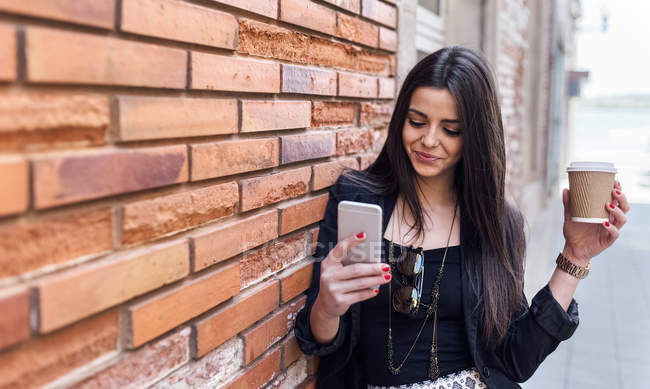 Young woman holding take away coffee and using smartphone, leaning on wall — Stock Photo