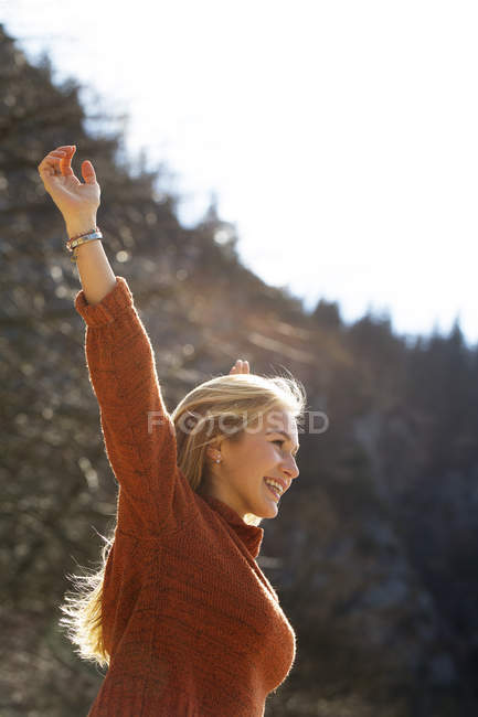 Happy teenage girl with raised arms in nature — Stock Photo