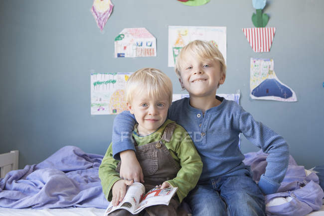 Portrait of two little brothers sitting on bed of children's room — Stock Photo