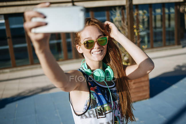 Smiling young woman wearing mirrored sunglasses taking selfie with smartphone — Stock Photo