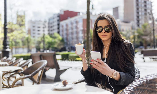 Pretty young woman having coffee at pavement cafe — Stock Photo
