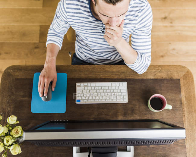 Man at wooden desk thinking — Stock Photo