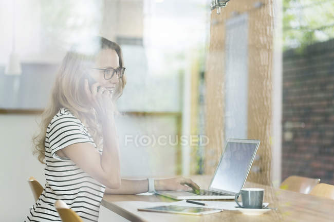 Mulher atrás da janela com telefone celular e laptop — Fotografia de Stock