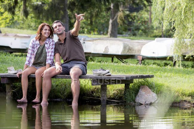 Pareja de jóvenes sentados en un muelle en el lago buscando a distancia - foto de stock