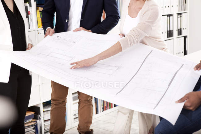 Four colleagues discussing construction plan in an office, partial view — Stock Photo