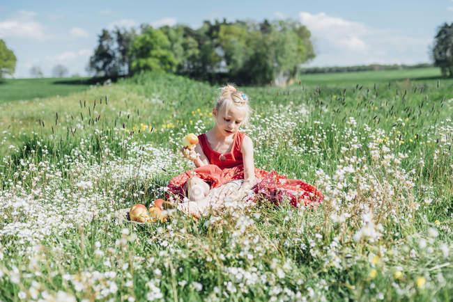 Chica sentado en flor prado - foto de stock