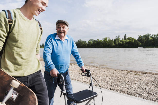 Grandfather and grandson strolling together at riverside — Stock Photo