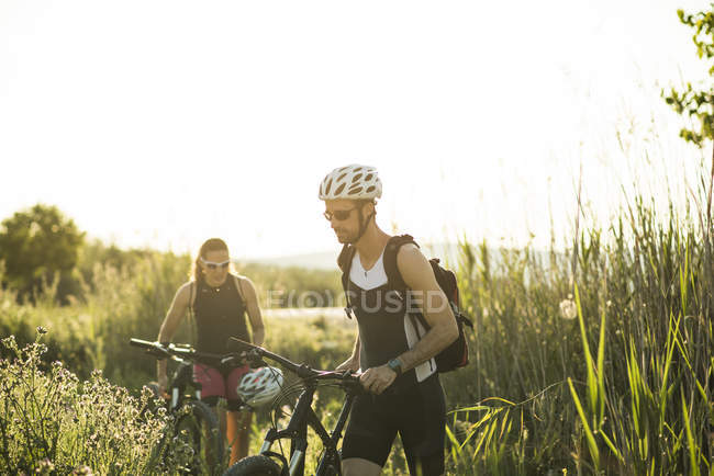 Two athletes pushing bicycles in rural landscape — Stock Photo