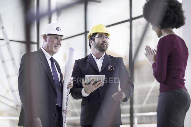 Two businessmen wearing hard hats talking to woman — Stock Photo