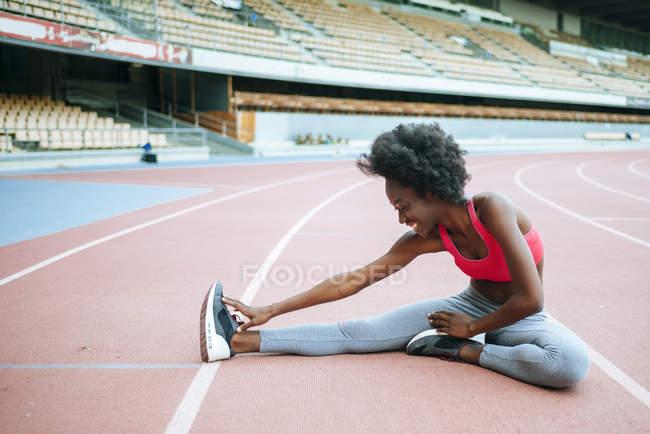 Jeune athlète féminine étirement avant course sur stade — Photo de stock