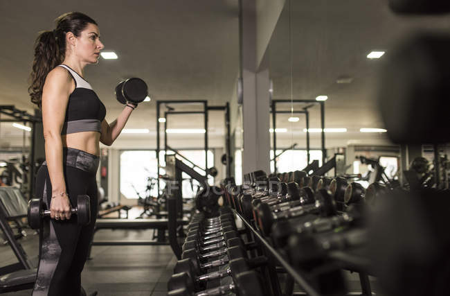 Mature woman training biceps, lifting dumbbells in gym — Stock Photo