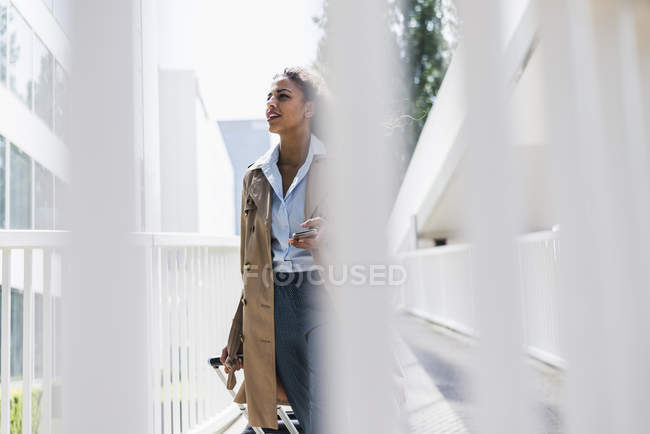 Young woman with luggage and cell phone on the move — Stock Photo