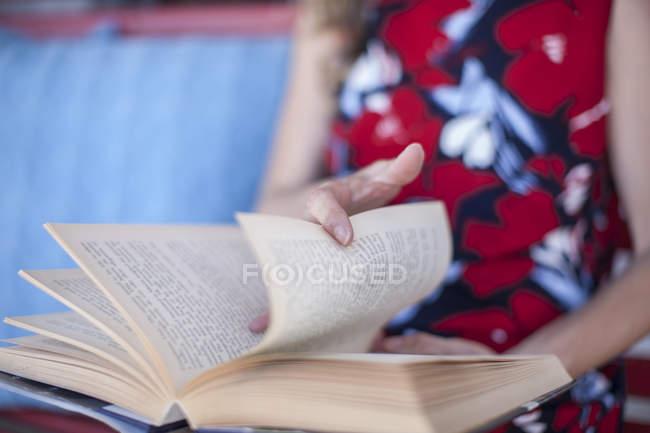 Обрезанный образ женщины, читающей книгу — стоковое фото