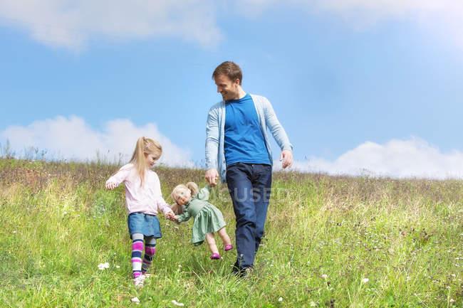 Pai feliz e filha andando com boneca no prado — Fotografia de Stock