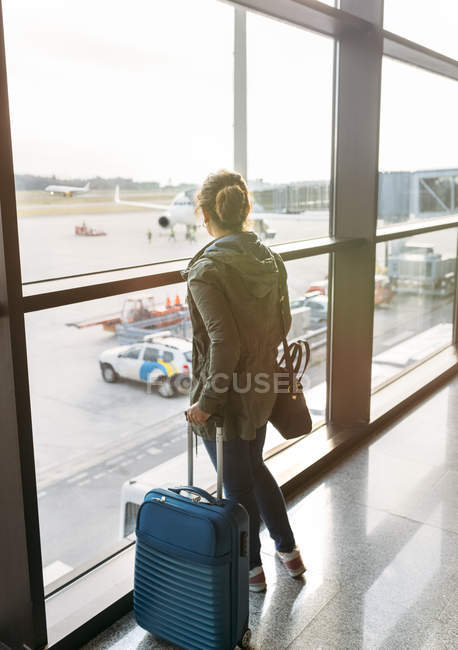 Woman waiting to boarding with suitcase in airport — Stock Photo