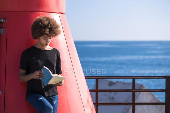 Junge Frau auf dem Deck ein Buch zu lesen — Stockfoto