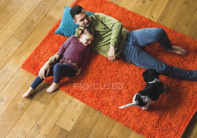 Батько і дочка, лежачи на килимі на підлозі з собакою — стокове фото