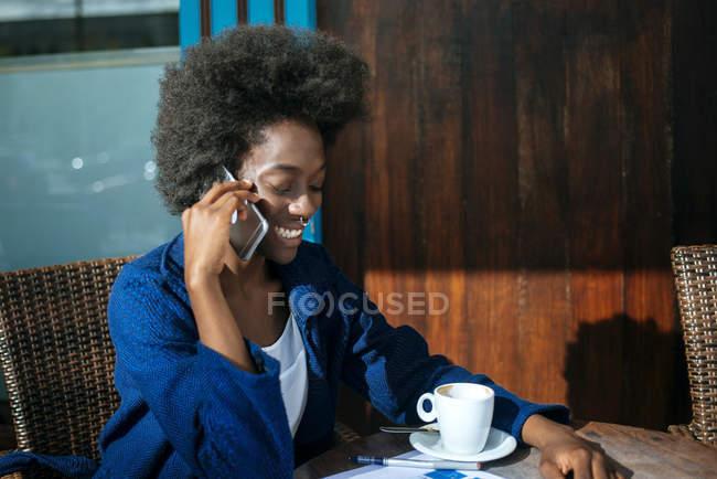 Ritratto di giovane donna che parla al cellulare mentre beve caffè in un caffè di strada — Foto stock