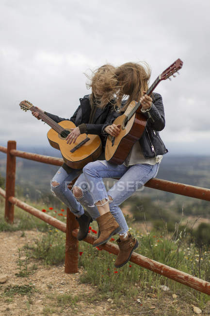 Two women sitting on wooden fence playing guitar — Stock Photo