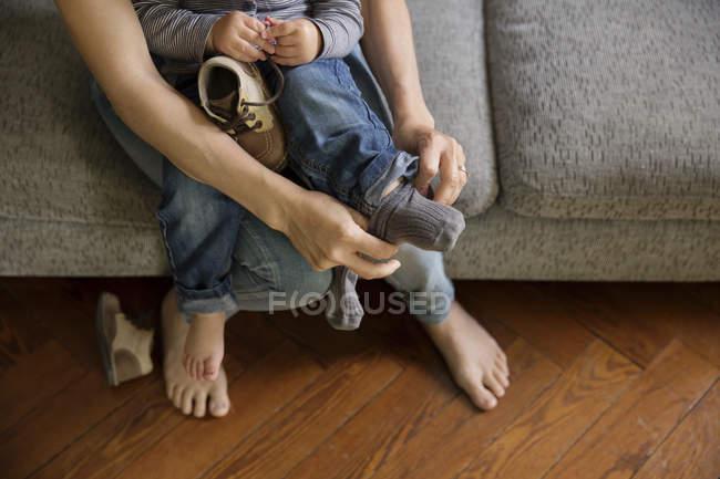 Manos de la madre ayudando a ponerse sus calcetines y zapatos de niño - foto de stock