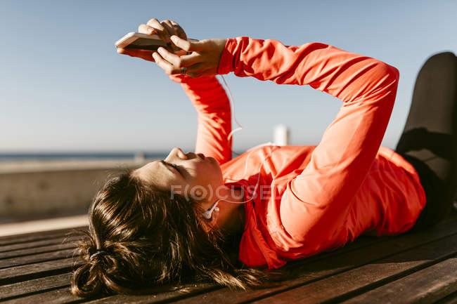 Femme au repos et en utilisant le téléphone après avoir exécuté — Photo de stock