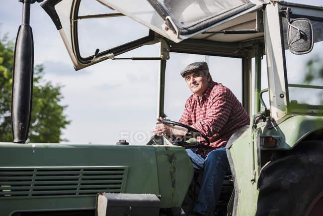 Paysan assis en tracteur — Photo de stock