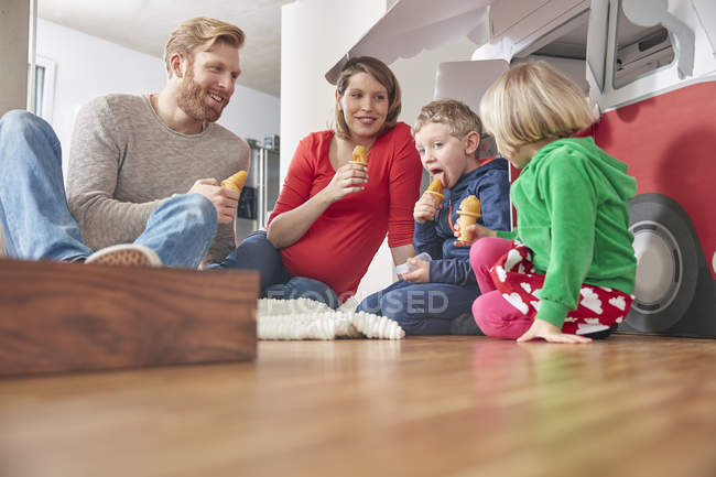 Happy family eating ice cream in living room — Stock Photo