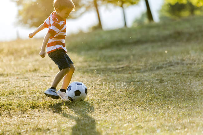 Little boy playing soccer on meadow — Stock Photo
