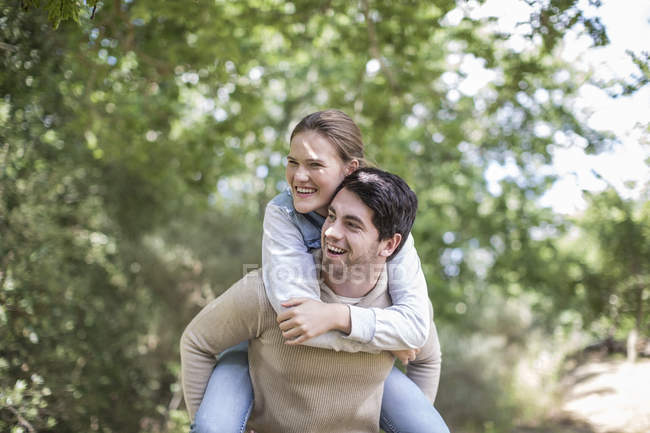 Young man carrying his girlfriend piggyback in the nature — Stock Photo