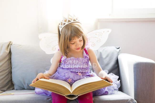 Портрет маленькой девочки в костюме королевы фей, читающей книгу — стоковое фото