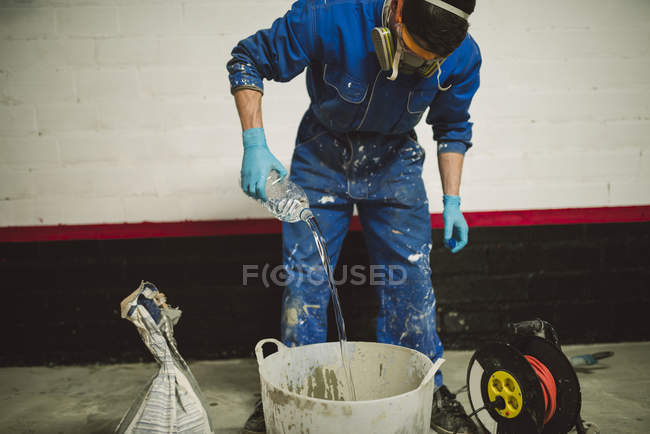 Bricklayer preparing cement in bucket, pouring water from bottle — Stock Photo