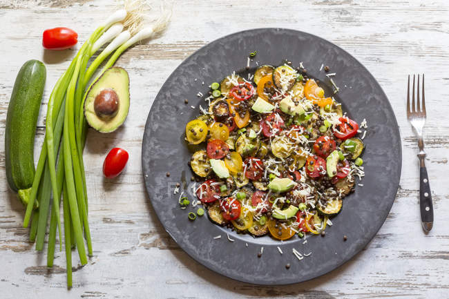 Vista superior del plato de ensalada de calabacín con aguacate, lentejas, cebolletas y queso - foto de stock