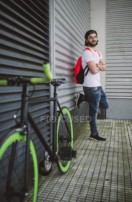 Giovane uomo appoggiato al muro accanto alla bici fixie — Foto stock
