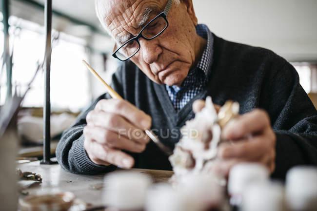 Senior man decorating ceramic in his spare time — Stock Photo