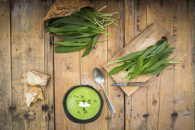 Bol de soupe à l'ail et Robert frais laisse sur bois — Photo de stock