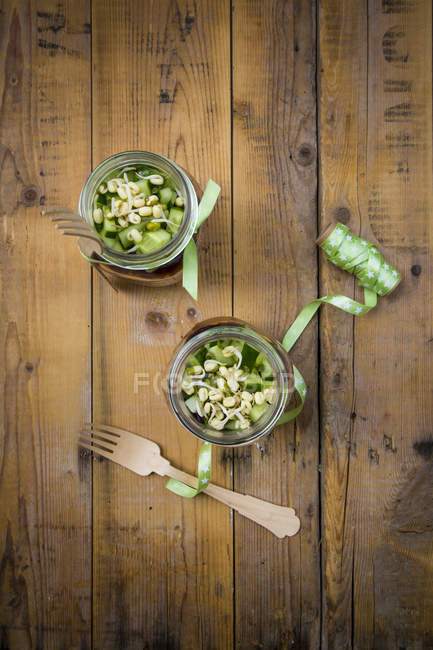 Two glasses of salad with sprouts and cucumber — Stock Photo