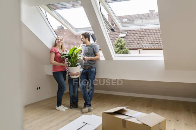 Familie Umzug in neues Zuhause und junge hält indoor-Anlage — Stockfoto