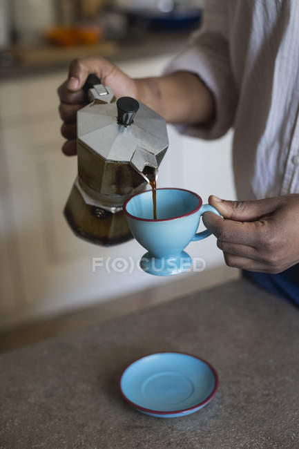 Young woman pouring espresso into cup, close-up — Stock Photo