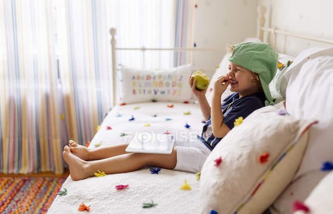 Сміючись маленький хлопчик, сидячи на дивані з apple і цифровий планшетний — стокове фото