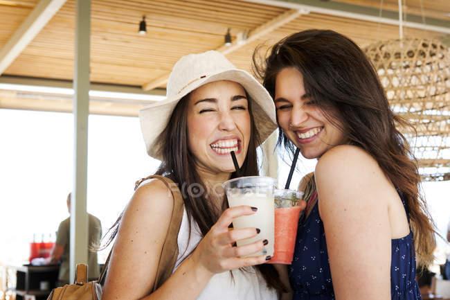 Dos jóvenes bebiendo cócteles en el bar de la playa - foto de stock