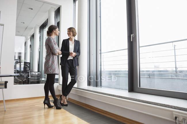 Два предпринимателей, говоря на окна в современном офисе — стоковое фото