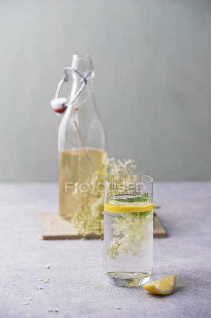 Glass of water flavoured with elderflower sirup and lemon — Stock Photo