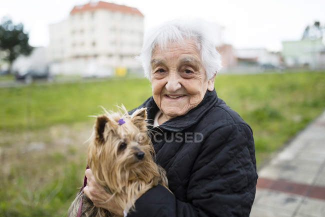 Portrait of senior woman with Yorkshire Terrier on her arms — Stock Photo